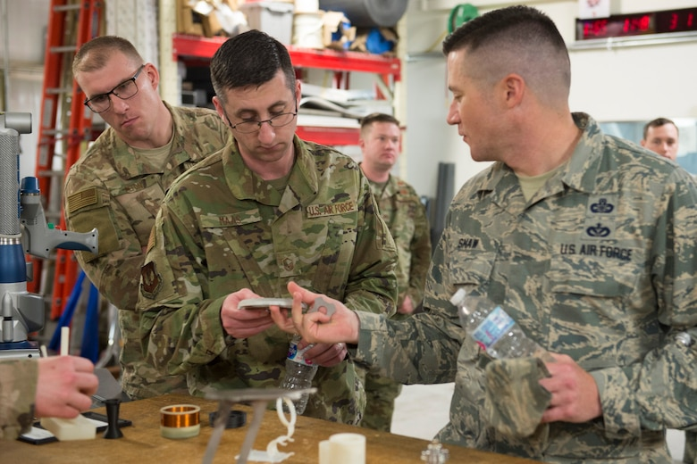 U.S. Air Force Master Sgt. Nathan Shaw (right), superintendent of the Air Force Technical Applications Center's Innovation Lab, shows Air Force Spark Tank winner Master Sgt. Jonathan Maas a project he's working on during a visit to the nuclear treaty monitoring center at Patrick Air Force Base, Florida, March 1, 2019. Looking over Mass' shoulder is Spark Tank finalist Staff Sgt. Travis W. Alton. (U.S. Air Force photo by Matthew S. Jurgens)