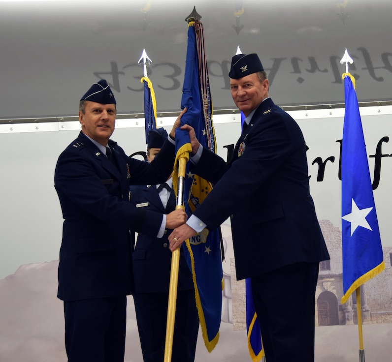 Maj. Gen. Randall A. Ogden, 4th Air Force commander, presents the wing guidon to Col. Terry W. McClain, 433rd Airlift Wing commander, at the 433rd AW change of command ceremony March 3, 2019 at Joint Base San Antonio-Lackland, Texas.