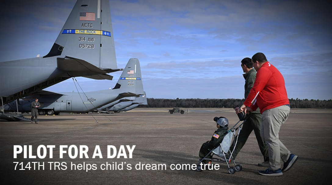 Two men wheel a child in a stroller out to a gray US Air Force plane.