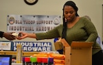 "DLA Troop Support Industrial Hardware employee and ""IH Trooper"" Temecca Baen places items in a ""Trooper Treat Box"" care package March 6, 2019 in Philadelphia."