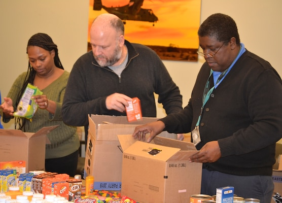 """DLA Troop Support Industrial Hardware employees and """"IH Troopers"""" Temecca Baen, Terry Piper and Ron Griffith, left to right, place items in a """"Trooper Treat Box"""" care package March 6, 2019 in Philadelphia."""