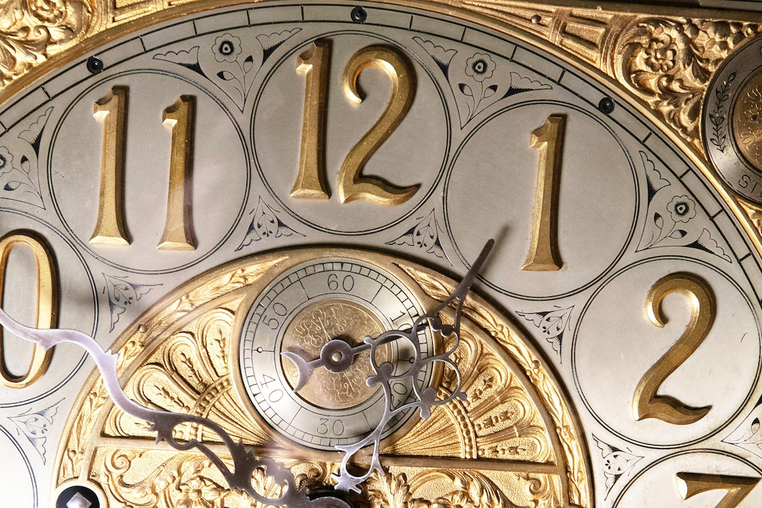 A close-up of an ornate silver and gold clock.