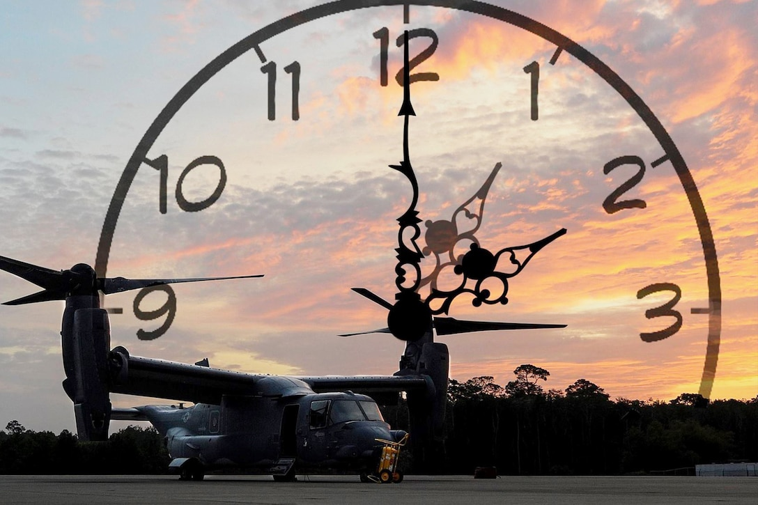 A CV-22 Osprey sits on a field at sunrise with a clock superimposed behind it.