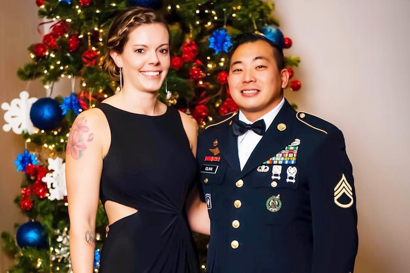 Soldier in uniform stands with wife in front of Christmas tree.