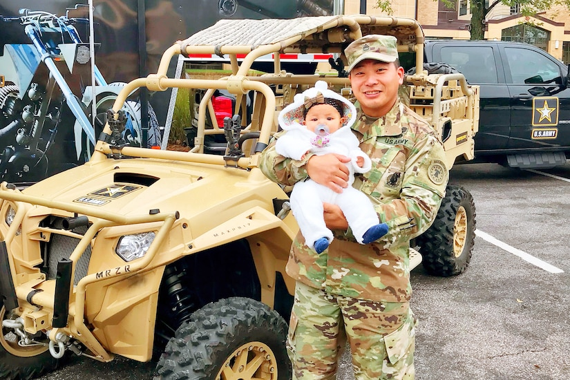 Soldier in uniform holds baby in front of all-terrain vehicle