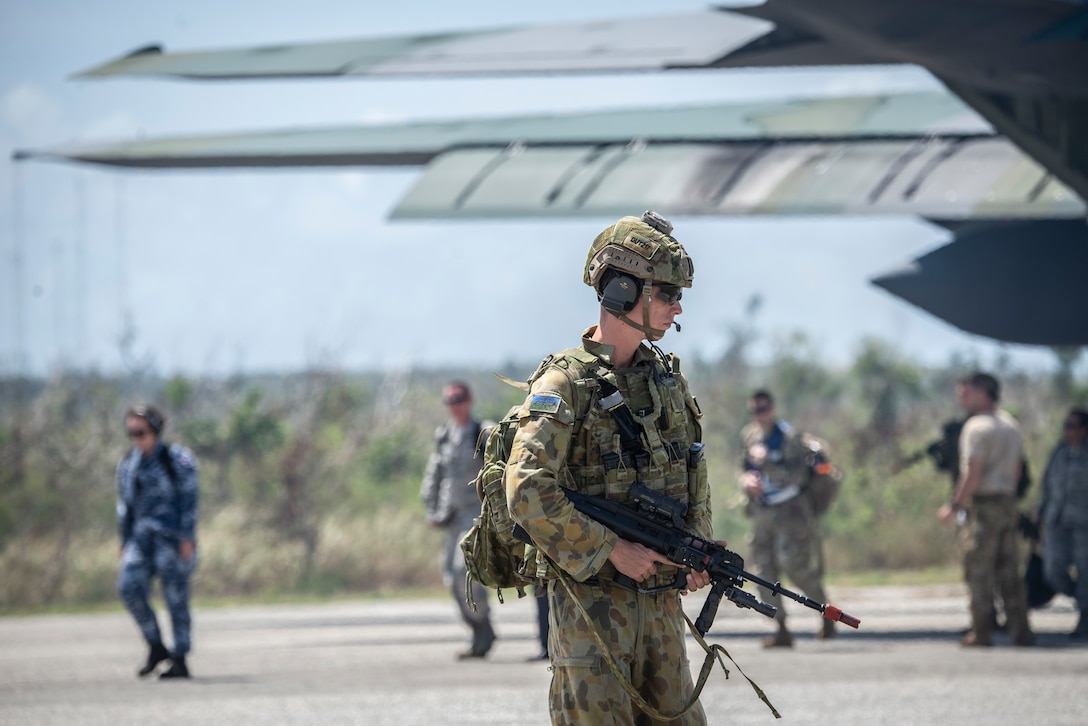 A Royal Australian air force member provides security for passengers exiting a plane during exercise Cope North at Tinian, U.S. Commonwealth of the Northern Marianas Islands stands, Feb. 19, 2019.