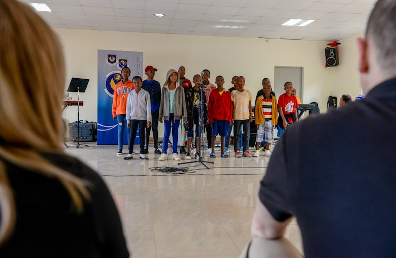 U.S. Airmen assigned to the U.S. Air Forces in Europe Band listen to a choir performance at the Gisimba Memorial Centre in Kigali, Rwanda, March 6, 2019. As musical ambassadors, members of the band can reach audiences that traditional military members can't. They travel the world to build cultural bridges, and honor and preserve cultural heritage. (U.S. Air Force photo by Tech. Sgt. Timothy Moore)