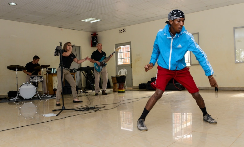 A student dances to music played by the U.S. Air Forces in Europe Band Touch N' Go during a performance at the Gisimba Memorial Centre in Kigali, Rwanda, March 6, 2019. As musical ambassadors, members of the band can reach audiences that traditional military members can't. They travel the world to build cultural bridges, and honor and preserve cultural heritage. (U.S. Air Force photo by Tech. Sgt. Timothy Moore)
