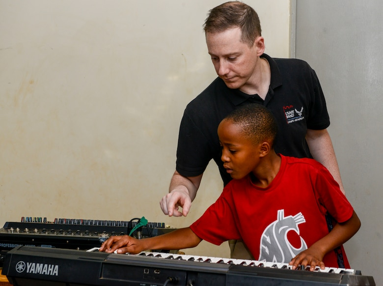 U.S. Air Force Staff Sgt. Justin Cockerham, U.S. Air Forces in Europe Band pianist, helps a student with find the right notes on a keyboard at the Gisimba Memorial Centre in Kigali, Rwanda, March 6, 2019. As musical ambassadors, members of the band can reach audiences that traditional military members can't. They travel the world to build cultural bridges, and honor and preserve cultural heritage. (U.S. Air Force photo by Tech. Sgt. Timothy Moore)
