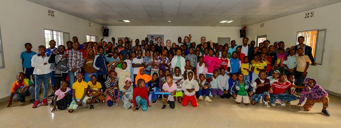 U.S. Airmen assigned to the U.S. Air Forces in Europe Band Touch N' Go pose for a photo with students and staff members at the Gisimba Memorial Centre in Kigali, Rwanda, March 6, 2019. As musical ambassadors, members of the band can reach audiences that traditional military members can't. They travel the world to build cultural bridges, and honor and preserve cultural heritage. (U.S. Air Force photo by Tech. Sgt. Timothy Moore)