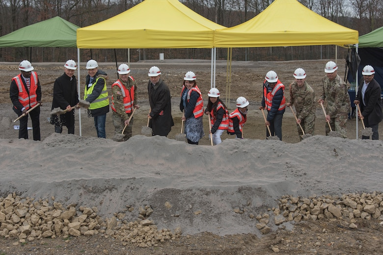 A group of people stand in a line with hard hats and orange safety vests, shoveling dirt.