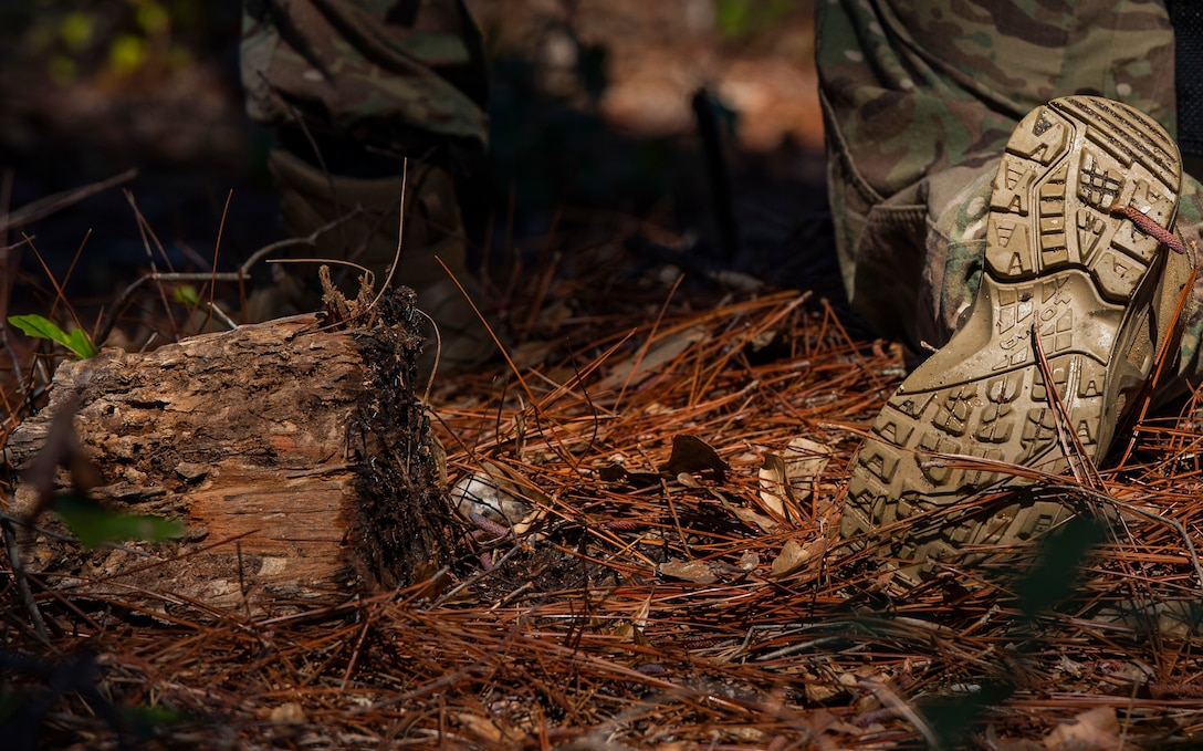 A U.S. Airman assigned to the 20th Security Force Squadron (SFS) kneels among straw during a force-on-force training at Poinsett Electronic Combat Range near Wedgefield, S.C., March 6, 2019.