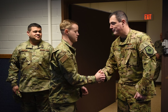 "Tech Sgt. Gabriel Vest, 86th Airlift Wing Maintenance Group, training management noncommissioned officer in charge shakes hands with Brig. Gen. Mark August, 86th AW commander accompanied by Chief Master Sgt. Ernesto Rendon, 86th AW command chief. Vest was named Airlifter of the Week, a program which recognizes Ramstein Airmen who are devoted to making the 86th AW the ""World's Best Wing."""