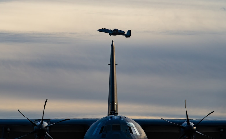 An A-10C Thunderbolt II flies over a C-130 J Hercules