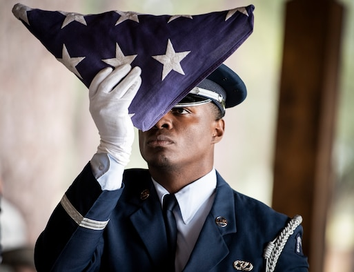 An Airman inspects a folded flag during an Honor Guard graduation ceremony