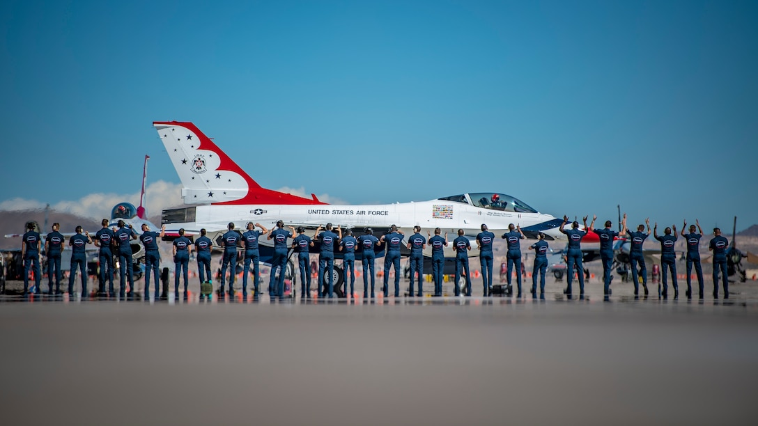 Thunderbird pilots stand on a flightine in front of a plane
