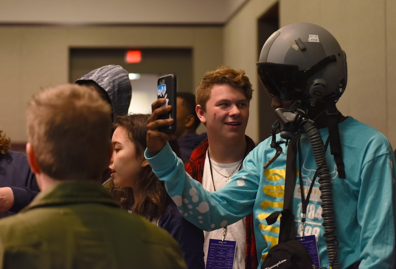 A high school student takes a photo while wearing a pilot helmet training at Mississippi State University's Engineering Day March 4, 2019, in Starkville, Mississippi. In addition to the VR technology, the pilots also taught the class about G-suits, pilot helmets and parachute harnesses; some of the gear necessary to fly in an Air Force aircraft. (U.S. Air Force photo by Senior Airman Beaux Hebert)