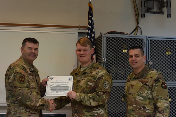 Col. Brian A. Filler, 39th Air Base Wing vice commander, left, and Chief Master Sgt. Jason  T. Heilman, 39th Air Base Wing command chief, right, present the Larger Than Life Award to Airman 1st Class Justin Warren, 39th Security Forces Squadron response force member, at Incirlik Air Base, Turkey, Mar. 6, 2019.