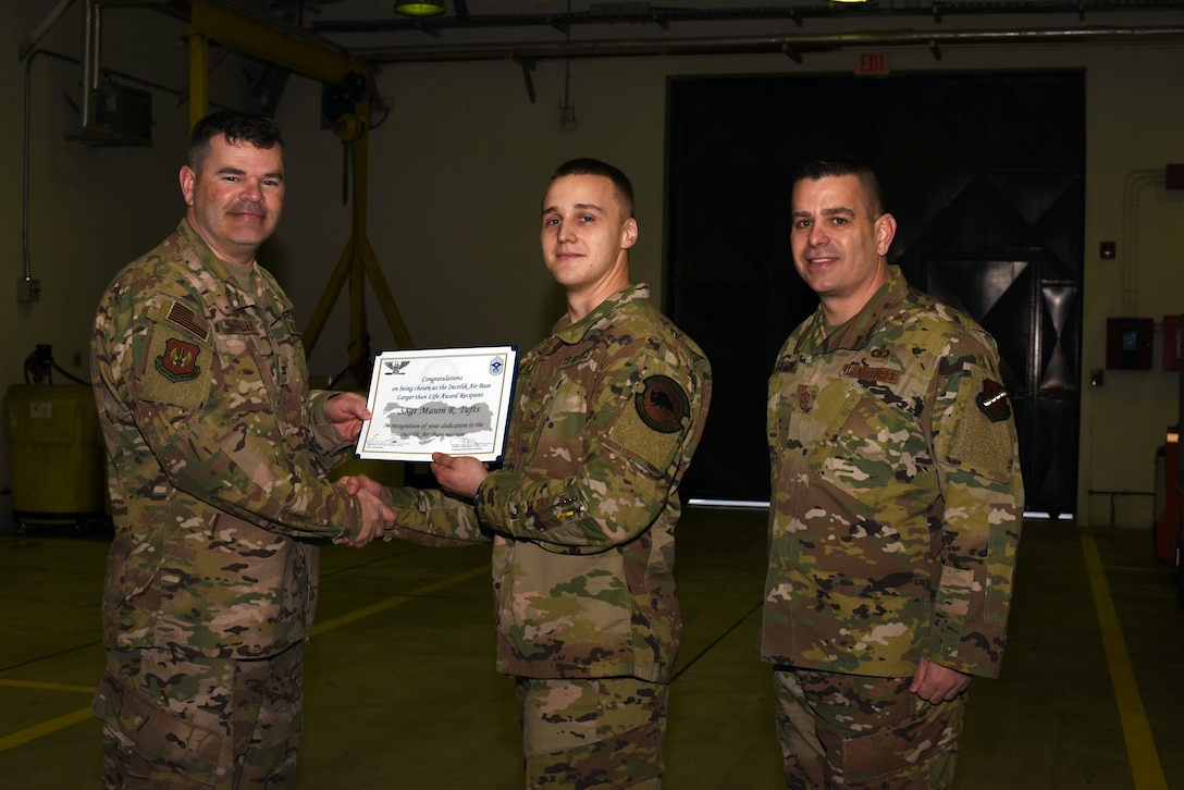 Col. Brian A. Filler, 39th Air Base Wing vice commander, left, and Chief Master Sgt. Jason T. Heilman, 39th Air Base Wing command chief, right, present the Larger Than Life Award to Staff Sgt. Mason Tufts, 39th Maintenance Squadron aerospace ground equipment journeyman, at Incirlik Air Base, Turkey, Mar. 6, 2019.