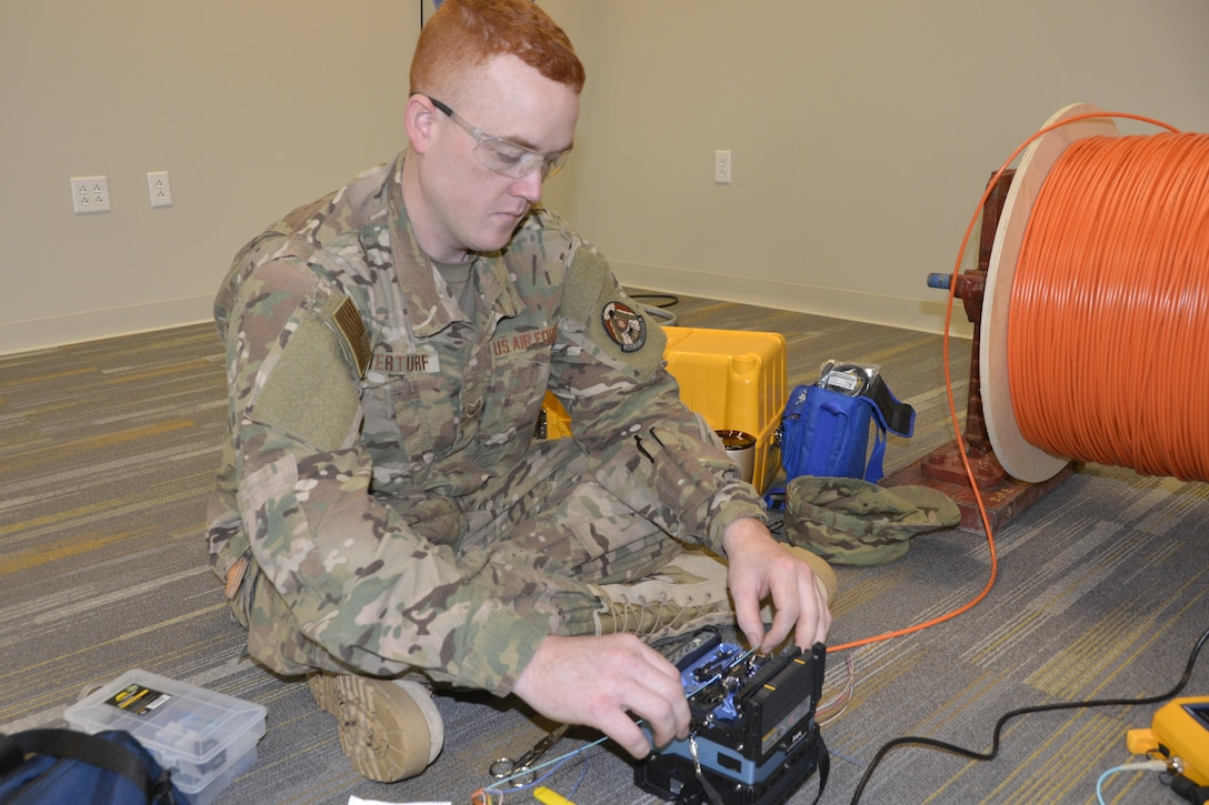 Staff Sgt. Jeremy Overturf, cable and antenna maintenance specialist with the 241st Engineering Installation Squadron, Chattanooga, Tenn., uses a fusion splicer to check new fiber optic cable prior to installation in a 1st Air Force (Air Forces Northern) Headquarters building office. Overturf is part of a group of seven Airmen from the 241st EIS who deployed here to assist the 1st AF (AFNORTH) enterprise to restore its communications and computer capabilities following the devastating effects of Hurricane Michael Oct. 10, 2018. (Air Force photo by Mary McHale)