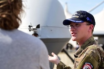 Staff Sgt. Dylan, MQ-9 Reaper avionics craftsman, explains the effects of taking the cockpit out of the aircraft to an airshow attendee during the Australian International Airshow, Mar. 3, 2019, in Geelong, Victoria, Australia. Over the week, the crews met with many of the airshow's more that 200,000 visitors and aviation fans. (U.S. Air Force photo by Airman 1st Class Haley Stevens)