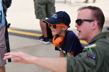 Capt. Daniel Bradfield, MQ-9 Reaper instructor pilot with the 49th Wing, talks with a child about the MQ-9's capabilities during the Australian International Airshow, Mar. 3, 2019, in Geelong, Victoria, Australia. Reaper crews have made their way across the United States to attend airshows such as this one, but this is their first time in the Pacific Air Forces Command area of responsibility and Australia. (U.S. Air Force photo by Airman 1st Class Haley Stevens)