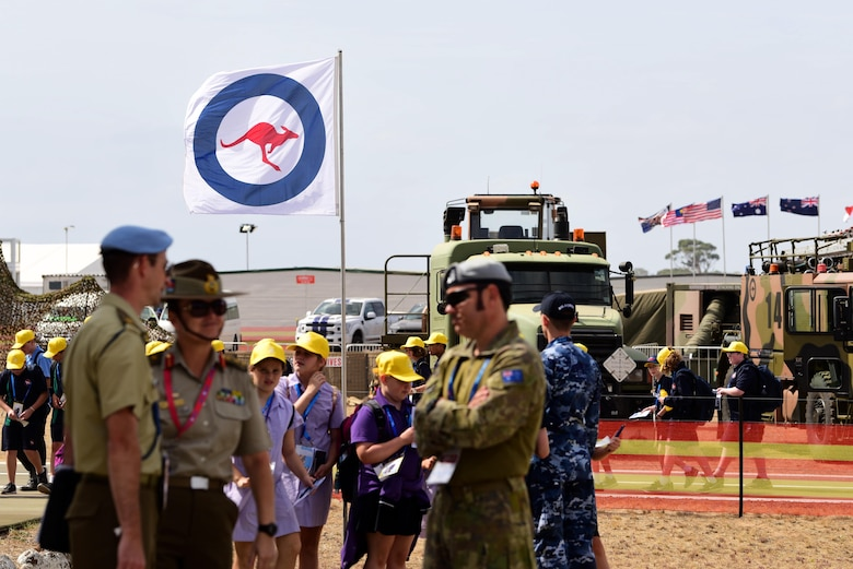 The Royal Australian Air Force emblem flag waves as airshow attendees explore the Australian International Airshow, Feb 26, 2019, in Geelong, Victoria, Australia. In line with the focus of strengthening the relationship between the Australian Defence Force and United States Military, the U.S. Air Force and Creech Airmen brought the Remotely Piloted Aircraft to be displayed during this airpower demonstration.(U.S. Air Force photo by Airman 1st Class Haley Stevens)