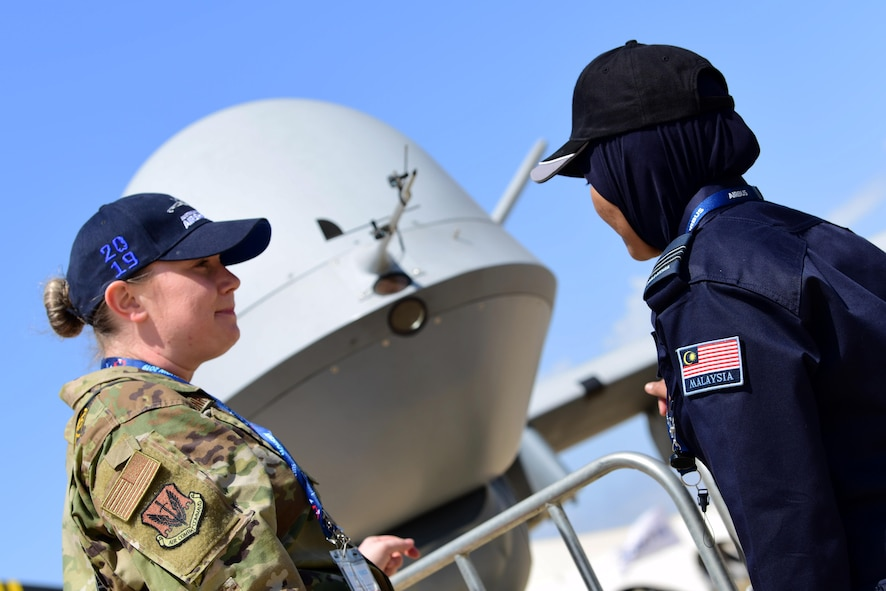 Capt. Annabel Monroe, 432nd Wing/432nd Air Expeditionary Wing Public Affairs officer, talks with an airshow visitor about the MQ-9 Reaper mission during the Australian International Airshow, Feb. 26, 2019, in Geelong, Victoria, Australia. Displaying the aircraft at the Australian International Airshow is not only an opportunity to help RPA Airmen explain their role in national security, but also provides the chance for the U.S. Air Force to show their support for our coalition partners in the Indo-Pacific region. (U.S. Air Force photo by Airman 1st Class Haley Stevens)