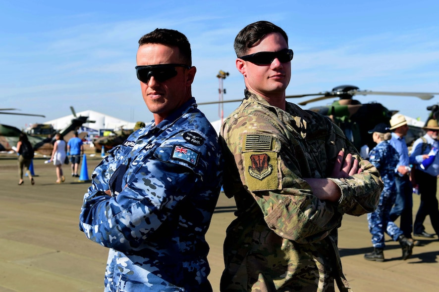 Aircraftman James Bayley with the Royal Australian Air Force, and Staff Sgt. Joshua with the United States Air Force display their national flags during the Australian International Airshow, Feb. 26, 2019, in Geelong, Victoria, Australia. In line with the focus of strengthening the relationship between the Australian Defence Force and U.S. military, the U.S. Air Force and Creech Airmen brought the MQ-9 Reaper to be displayed during this airpower demonstration. (U.S. Air Force photo by Airman 1st Class Haley Stevens)