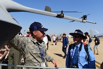 Senior Airman Issac Solis, MQ-9 Reaper crew chief, explains the purpose of different parts of the aircraft during the Australian International Airshow, Mar. 2, 2019, in Geelong, Victoria, Australia. Displaying the aircraft at the Australian International Airshow is not only an opportunity to help RPA Airmen explain their role in national security, but also provides the chance for the U.S. Air Force to show their support for our coalition partners in the Indo-Pacific region. (U.S. Air Force photo by Airman 1st Class Haley Stevens)