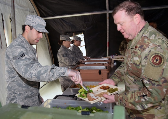 Senior Airman Jacob Livar (left), 433rd Force Support Squadron fitness specialist, serves a meal to Lt. Gen. Richard Scobee (right) , commander of the Air Force Reserve Command at Joint Base San Antonio-Lackland March 2. Scobee visited several organizations in the 433rd Airlift Wing.