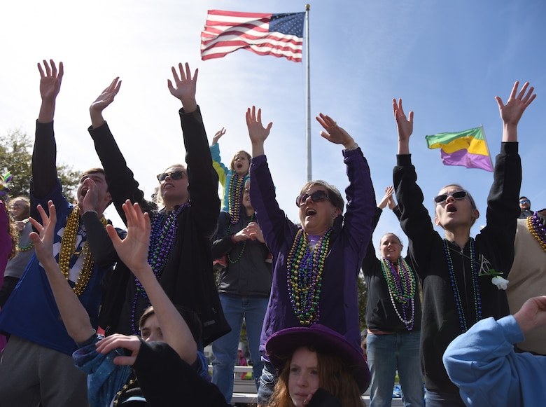 "Keesler personnel and their families raise their hands and yell for ""throws"" from parade floats during the Gulf Coast Carnival Association Mardi Gras parade in Biloxi, Mississippi, March 5, 2019. Keesler personnel participate in local parades every Mardi Gras season to show their support of the communities surrounding the installation. (U.S. Air Force photo by Kemberly Groue)"