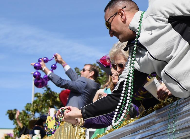 U.S. Air Force Chief Master Sgt. Ricardo Russo, Keesler Medical Center superintendent, reaches for a strand of beads tossed from floats during the Gulf Coast Carnival Association Mardi Gras parade in Biloxi, Mississippi, March 5, 2019. Keesler personnel participate in local parades every Mardi Gras season to show their support of the communities surrounding the installation. (U.S. Air Force photo by Kemberly Groue)