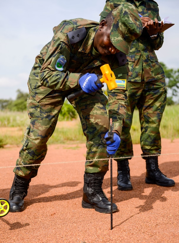 A Rwanda Defence Force member hammers a rod into the ground during the African Partnership Flight Rwanda field familiarization exercise at the Rwanda Military Academy in Gako, Rwanda, March 7, 2019. Throughout the weeklong African Partnership Flight, participants discussed various aspects of safety, with each country discussing how they conduct their programs, culminating with teams investigating a simulated aircraft crash in the field familiarization exercise. (U.S. Air Force photo by Tech. Sgt. Timothy Moore)
