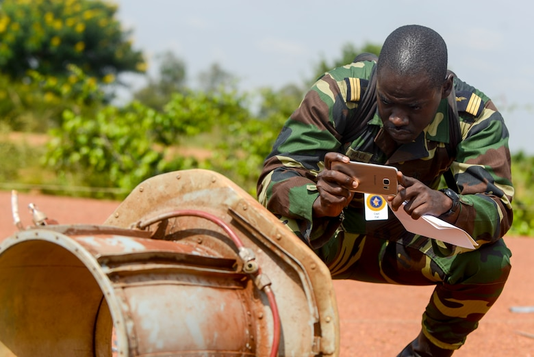 Senegal Air Force Capt. Mar Fall takes a photo of an aircraft part during the African Partnership Flight Rwanda field familiarization exercise at the Rwanda Military Academy in Gako, Rwanda, March 7, 2019. Throughout the weeklong African Partnership Flight, participants discussed various aspects of safety, with each country discussing how they conduct their programs, culminating with teams investigating a simulated aircraft crash in the field familiarization exercise. (U.S. Air Force photo by Tech. Sgt. Timothy Moore)