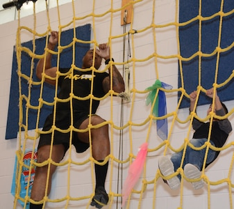 A Soldier leads a student on the cargo climbing net. A group of Soldiers and Sailors joined Colonial Hills Elementary School students at their Heroes for Health Day Feb. 28.