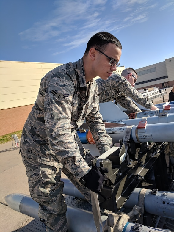 A1C Dylan Dodd secures bombs to a bomb rack