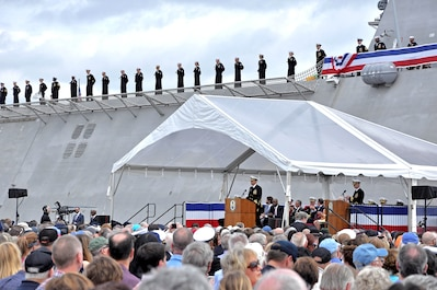 Cmdr. Christopher K. Brusca, the commanding officer of the Navy's newest littoral combat ship, USS Charleston (LCS 18), delivers his remarks while his crew watch on from the ship during the commissioning ceremony.
