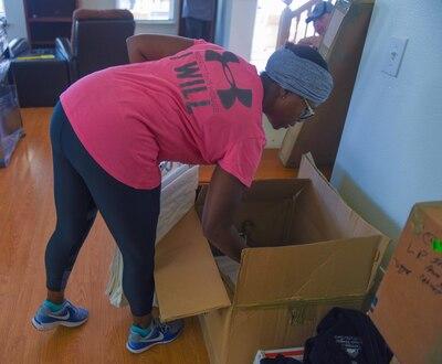 A woman unpacks a box.