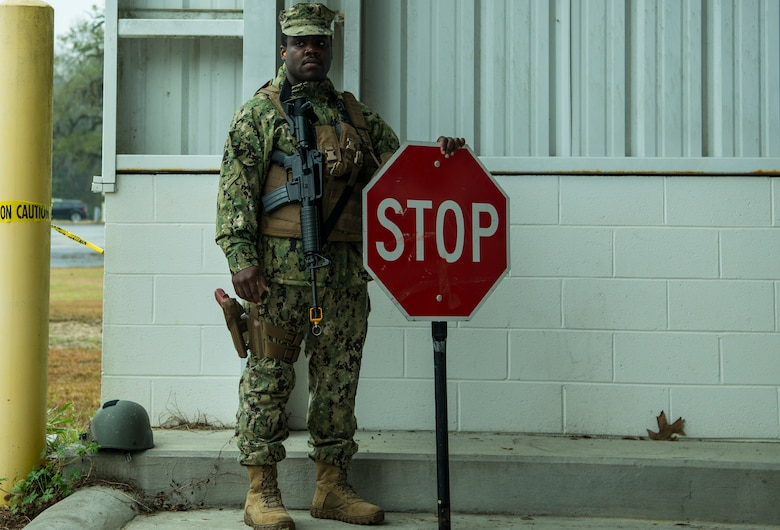 Gunners Mate Petty Officer 2nd Class Robert Dostaly, Coastal Riverine Squadron 10 Bravo 2nd Platoon, holds a stop sign during a deployment exercise March 5, 2019, at Joint Base Charleston, S.C. -- Naval Weapons Station.