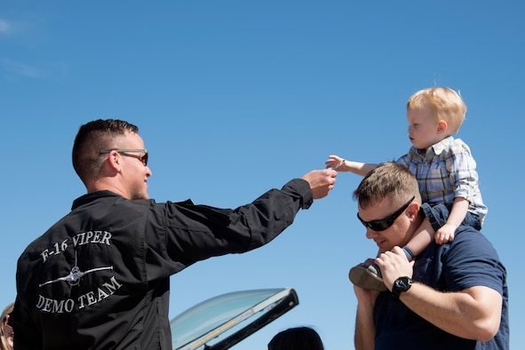 U.S. Air Force Staff Sgt. Trevor Griswold, F-16 Viper Demonstration Team electrical and environmental systems craftsman, hand a sticker to a child on the flight line at Davis-Monthan Air Force Base, Ariz., March 3, 2019.