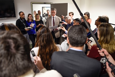 A man is surrounded by reporters as he speaks.