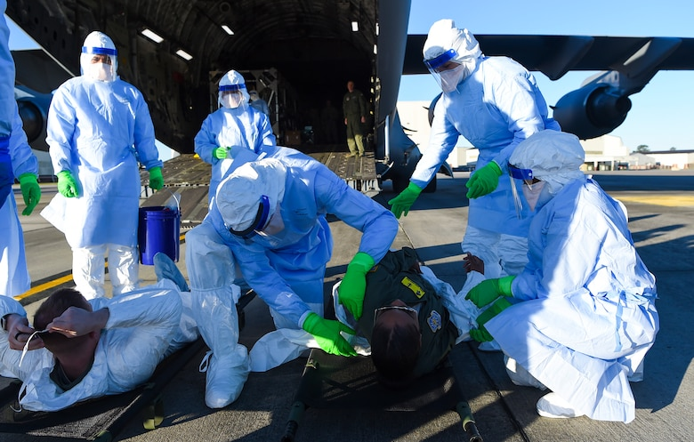 Airmen taking part in transportation isolation system training March 6, 2019, attend to simulated patients during an exercise designed to enhance how the Air Force transports patients and their medical professionals at Joint Base Charleston, S.C. Engineered and implemented after the Ebola virus outbreak in 2014, the TIS is an enclosure the Department of Defense can use to safely transport patients with highly contagious diseases.