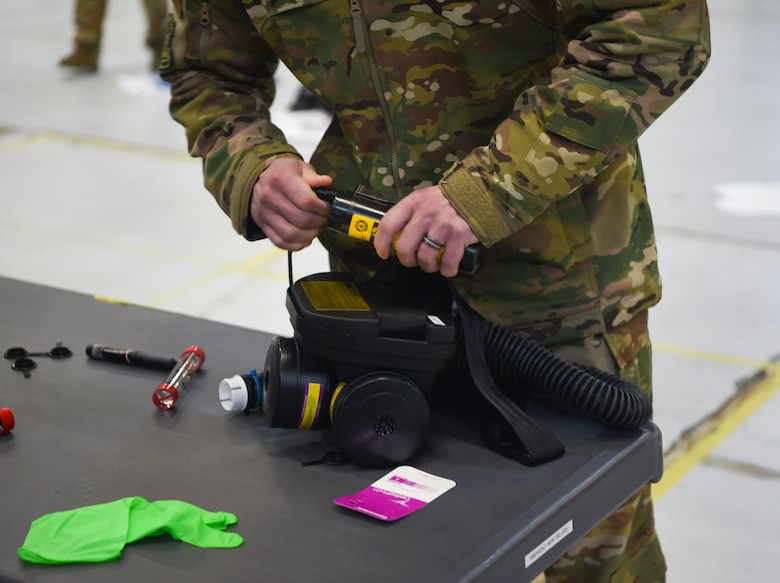 An Airman prepares and inspects his gear before donning personal protective equipment March 5, 2019 during transportation isolation system training at Joint Base Charleston, S.C. Engineered and implemented after the Ebola virus outbreak in 2014, the TIS is an enclosure the Department of Defense can use to safely transport patients with highly contagious diseases.