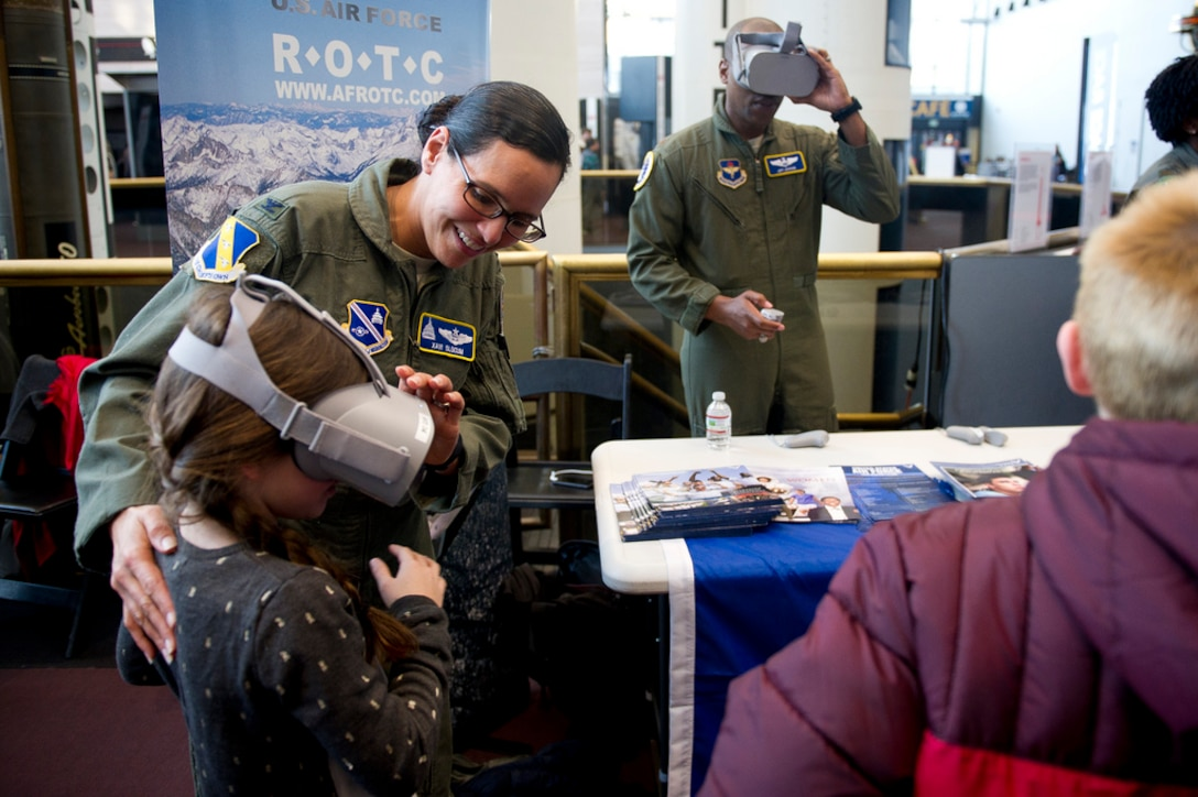U.S. Air Force Col. Xavi Slocum, the Individual Mobilization Augmentee to the Air Force District of Washington commander, helps her daughter with a virtual reality headset during the release of Captain Marvel and Air Force STEM fair at the Smithsonian National Air and Space Museum in Washington D.C., March 7, 2019. (U.S. Air Force photo by Master Sgt. Michael B. Keller)