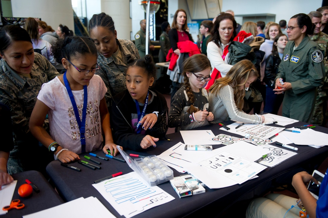 Air Force District of Washington and Air Combat Command Airmen and their daughters create paths for small robots during the Air Force STEM fair at the Smithsonian National Air and Space Museum in Washington D.C., March 7, 2019. (U.S. Air Force photo by Master Sgt. Michael B. Keller)