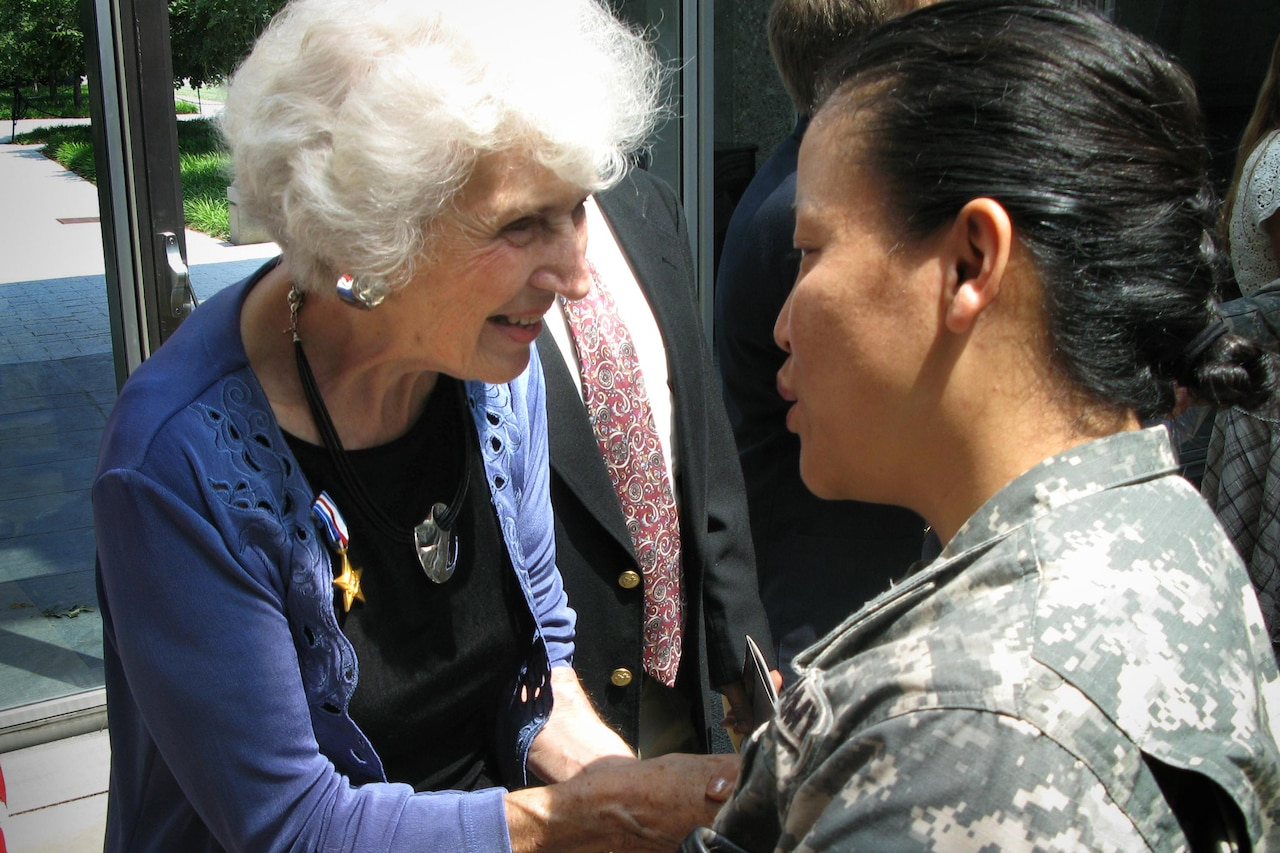 A civilian woman wearing a Silver Star talks with a soldier.