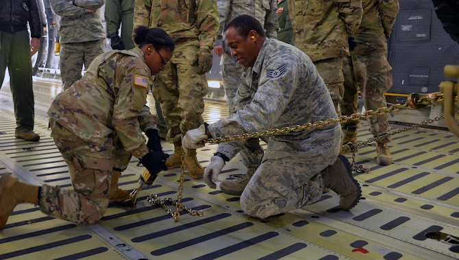 Air Force Staff Sgt. Wayne Burke, 26th Aerial Port Squadron air transportation specialist, instructs Army Private First Class Shakirra Hoyte, 13th Expeditionary Sustainment Command, on how to secure a vehicle for air transportation in a C-5M Super Galaxy aircraft March 2, 2019 at Joint Base San Antonio-Lackland, Texas.