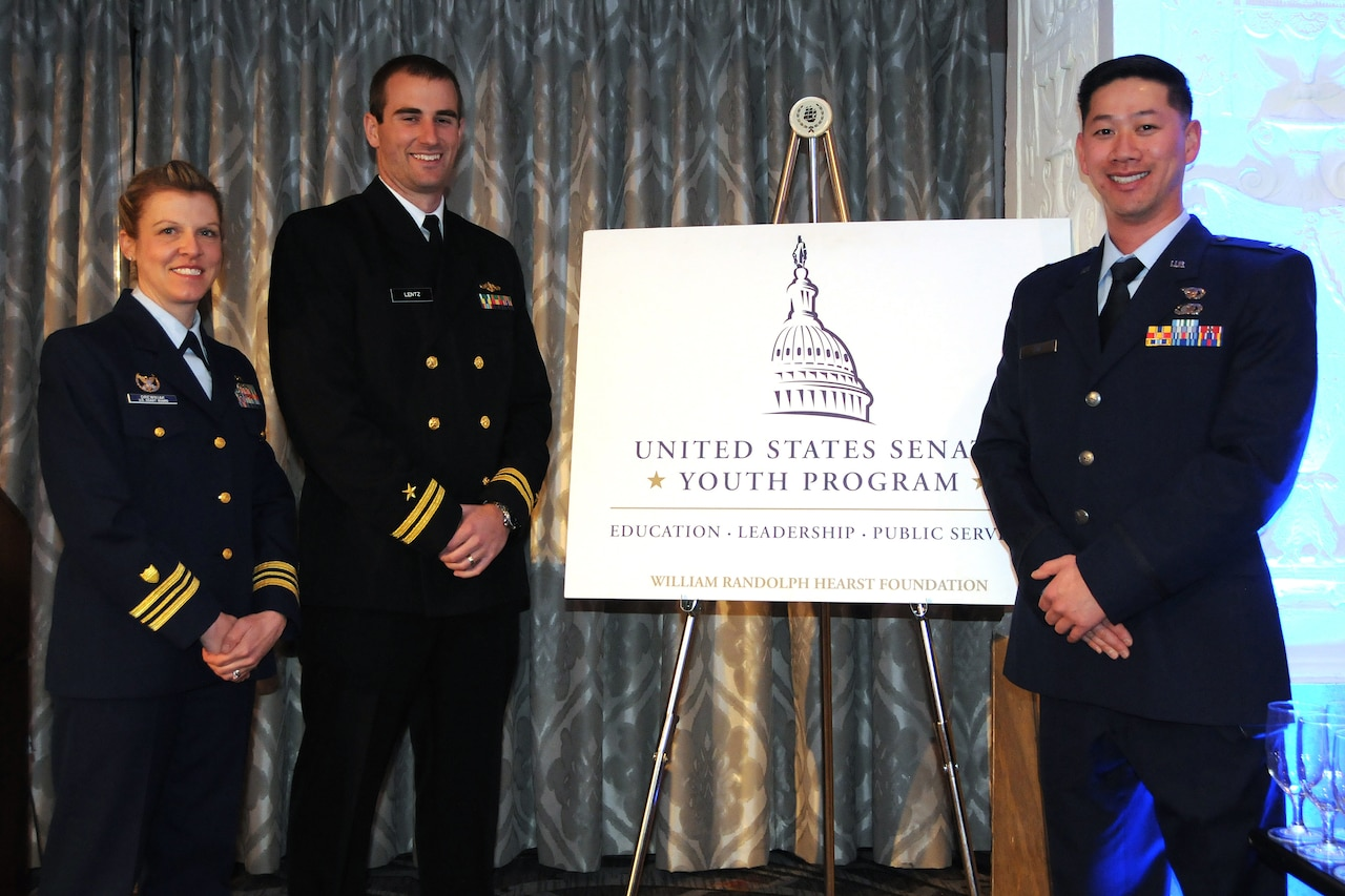 Three military officers stand in front of sign.