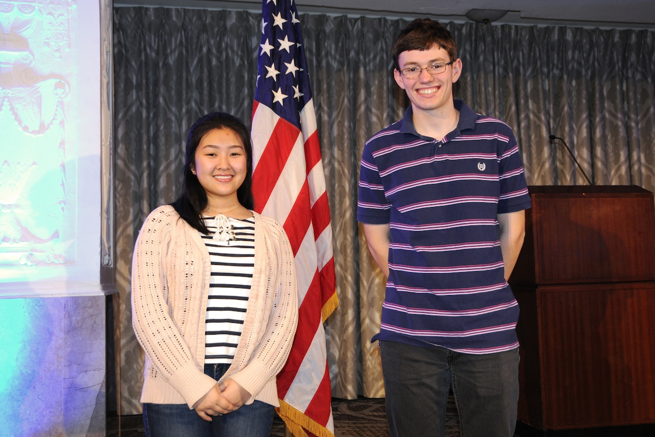 Two teenagers stand in front of a flag.